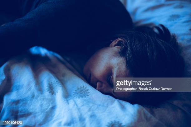 a woman sleeping in bed at night time - sleeping stock pictures, royalty-free photos & images