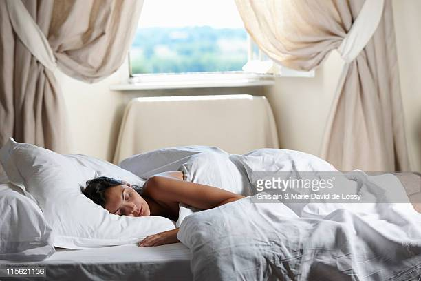 Woman sleeping in bed, by the window