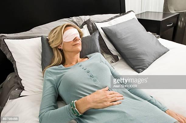 Woman sleeping in bed wearing an eye mask