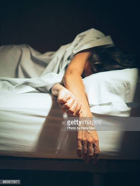 Woman sleeping in bed with arms hanging over edge
