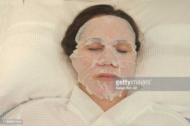 woman sleeping in bed with face mask - rafael ben ari imagens e fotografias de stock