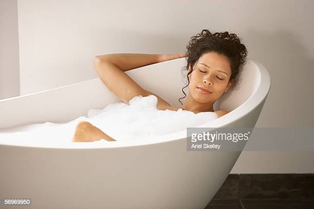 Woman sleeping in bubble bath