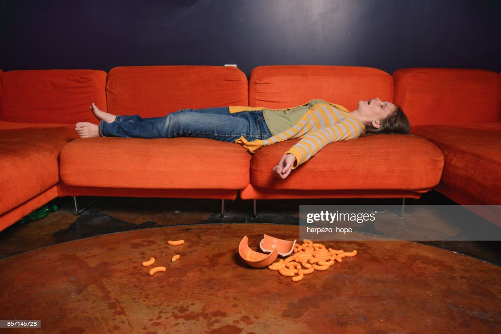 Woman sleeping on a sofa and cheese puffs on the floor. : Stock Photo