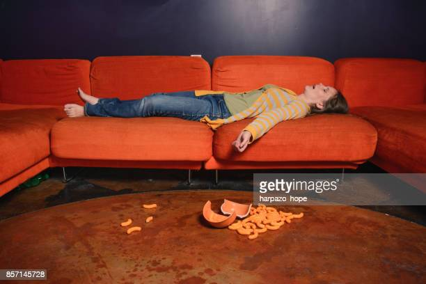 woman sleeping on a sofa and cheese puffs on the floor. - dormir humour photos et images de collection