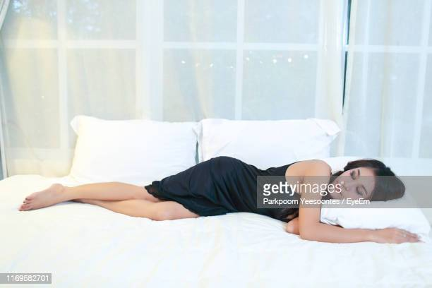 woman sleeping on bed - nightdress stock pictures, royalty-free photos & images