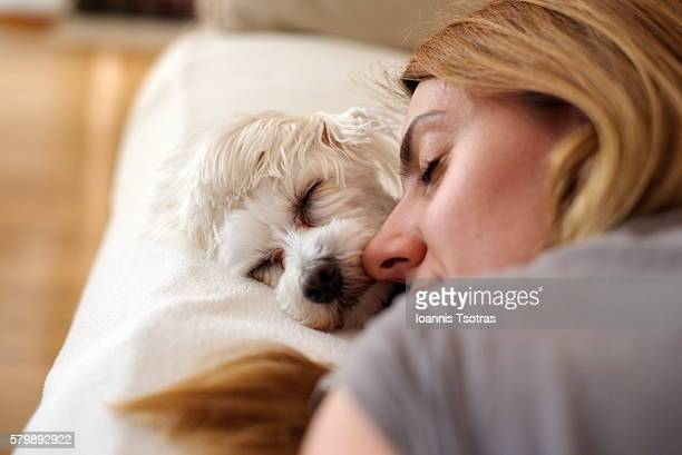 Woman sleeping on bed with dog