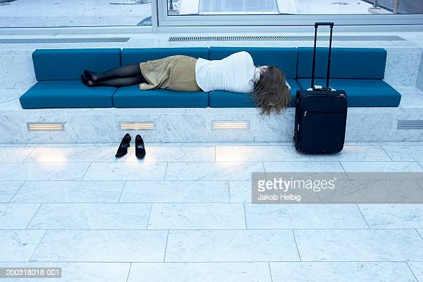 Woman sleeping on bench in airport, rear view