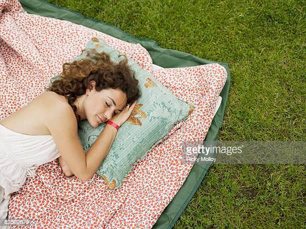 Woman sleeping on blanket outside