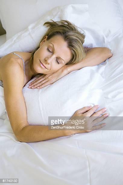 woman sleeping on comfortable pillow, high angle view - acostado boca abajo fotografías e imágenes de stock