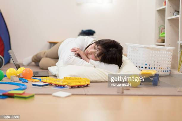 woman sleeping on floor full of toy - homemaker stock pictures, royalty-free photos & images