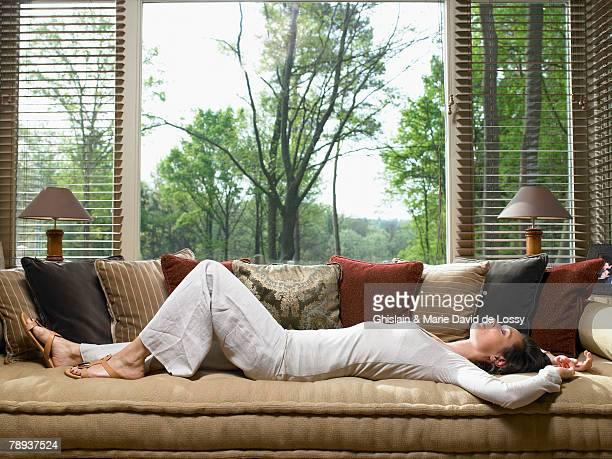 Woman sleeping on sofa in living room.
