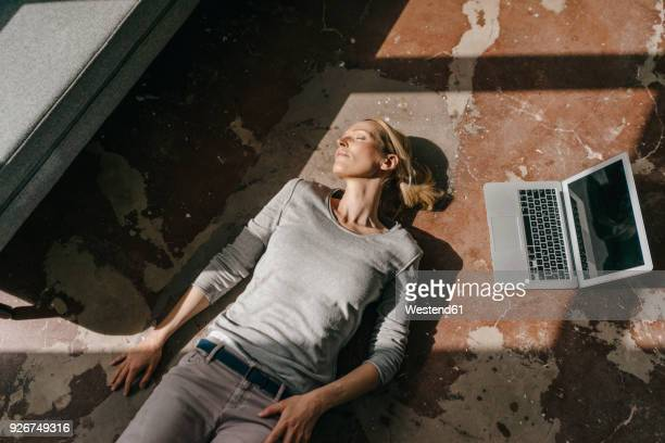 woman sleeping on the floor next to laptop - ruhen stock-fotos und bilder