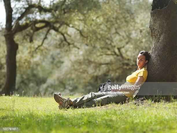 woman sleeping under a tree - zurücklehnen stock-fotos und bilder