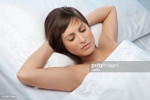 Woman Sleeping With Arms Over Her Head