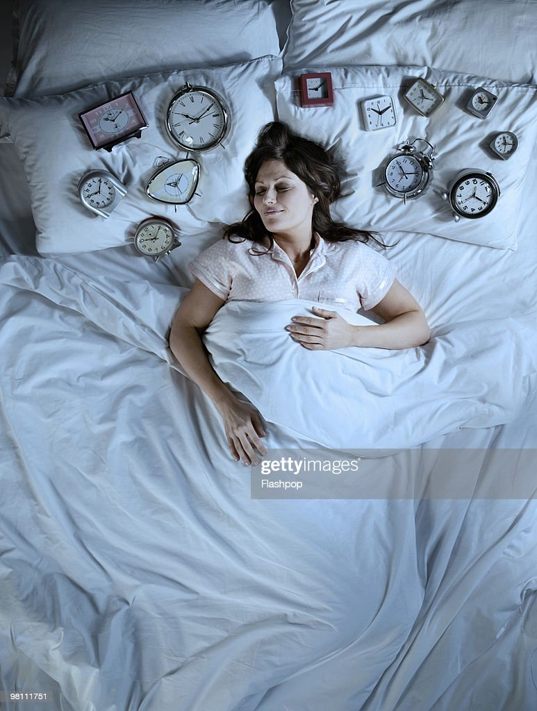 Woman Sleeping With Lots Of Alarm Clocks Stock Photo Getty Images