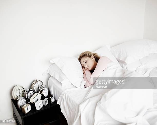 Woman sleeping with lots of alarm clocks
