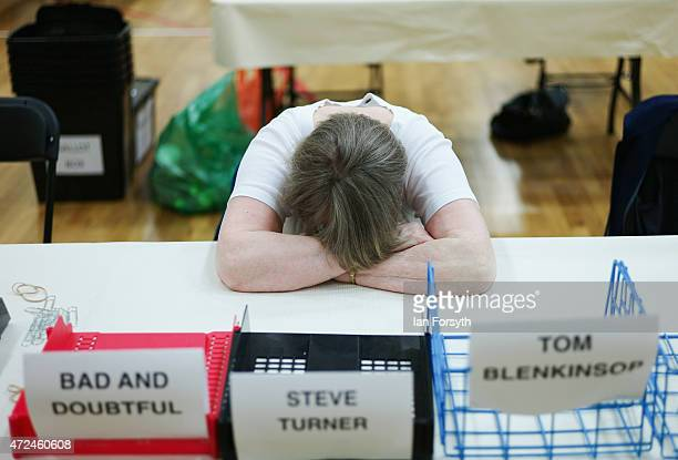 A woman sleeps as she waits for ballot papers to arrive during the Middlesbrough and East Cleveland Count on May 8 2015 in Redcar England The United...
