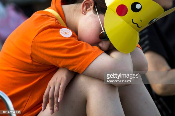 A woman sleeps as she waits for performers dressed as Pikachu a character from Pokemon series game titles during the Pikachu Outbreak event hosted by...