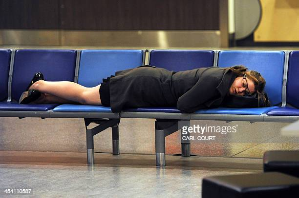 """Woman sleeps at Gatwick Airport in southern England on December 7, 2013. A """"technical problem"""" in Britain's air traffic control systems caused..."""
