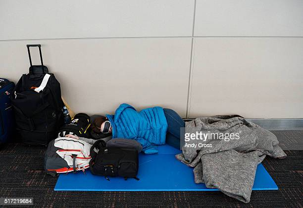 A woman sleeps in a hallway above the south security check point at Denver International Airport March 24 2016 Thousands of passengers that were...