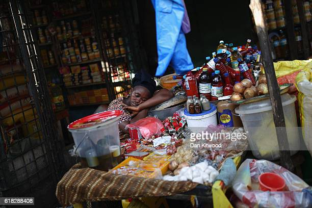 A woman sleeps in a market area on November 19 2015 in Conakry Guinea Guinea is currently counting down the necessary 42 days period required without...