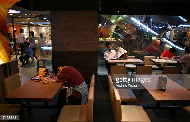 A woman sleeps in a restaurant on June 26 2007 in Hong Kong After hitting bottom following the SARS epidemic in the spring of 2003 the local economy...