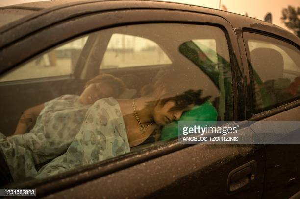 Woman sleeps in her car on the beach as wildfire rages in Pefki village on Evia island, second largest Greek island, on August 8, 2021. - Hundreds of...