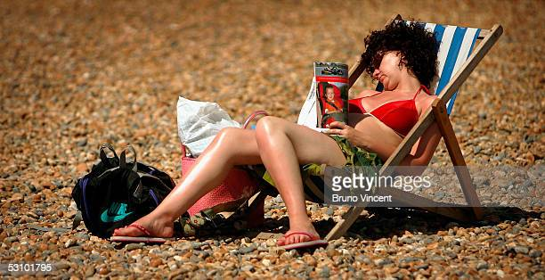 A woman sleeps in the sun on Brighton Beach on June 19 2005 in Brighton England Temperatures are likely to soar to 33C in London with similar highs...