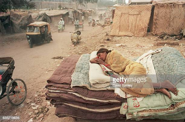 Woman sleeps on a pile of quilts beside a dusty road in a refugee camp on the outskirts of New Delhi. The camp sprung up to house people escaping...