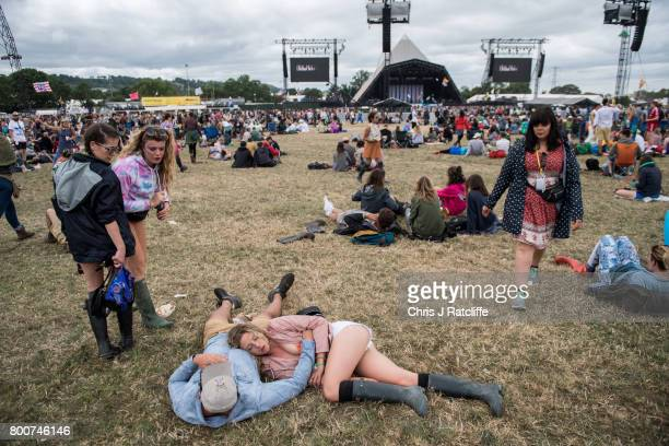 A woman sleeps on her partner's chest during the afternoon at the Pyramid Stage at Glastonbury Festival Site on June 25 2017 in Glastonbury England...
