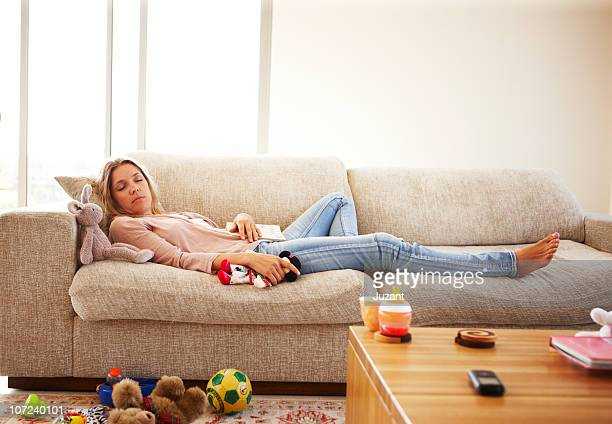 Woman sleeps on sofa surrounded by toys