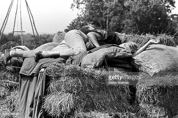 A woman sleeps on top of a pile of hay at the Woodstock Music Art Fair Bethel NY August 15 1969
