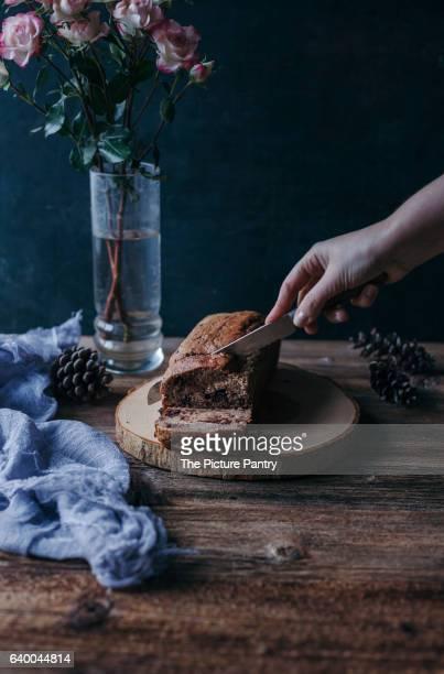 Woman slicing Banana chocolate chip bread