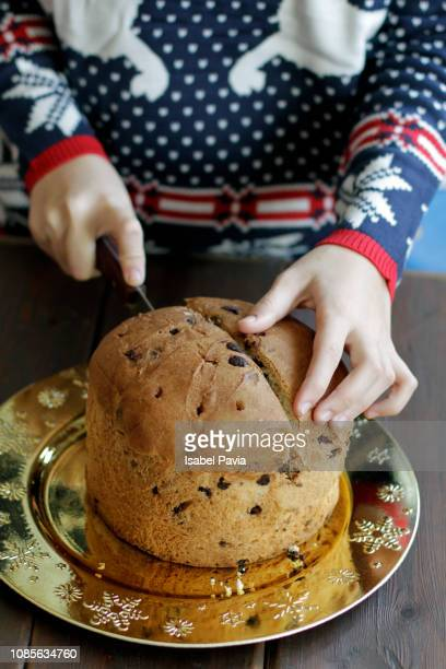 woman slicing christmas panettone - panettone stock pictures, royalty-free photos & images