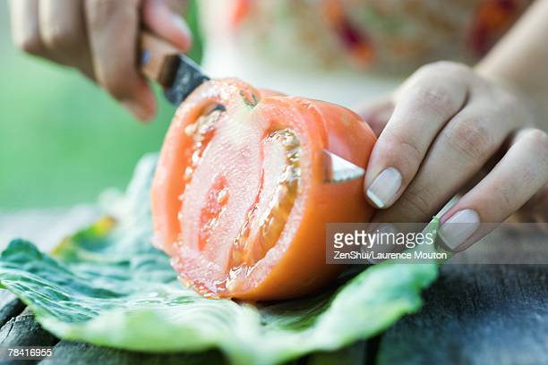 Woman slicing tomato, close-up, cropped view of hands