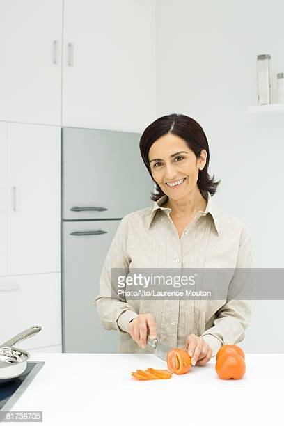 Woman slicing tomatoes in kitchen