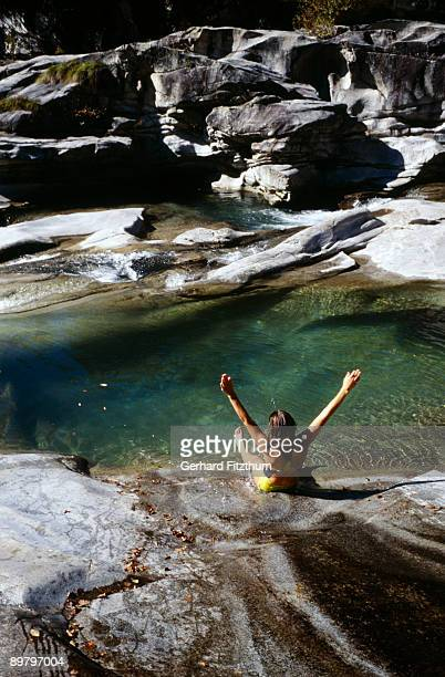 A woman sliding down rocks into a pool of water, Piedmont, Italy