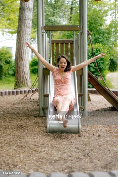 woman sliding on a slide on a playground - 滑る ストックフォトと画像