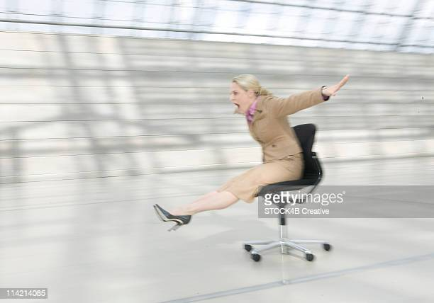 Woman sliding with office chair