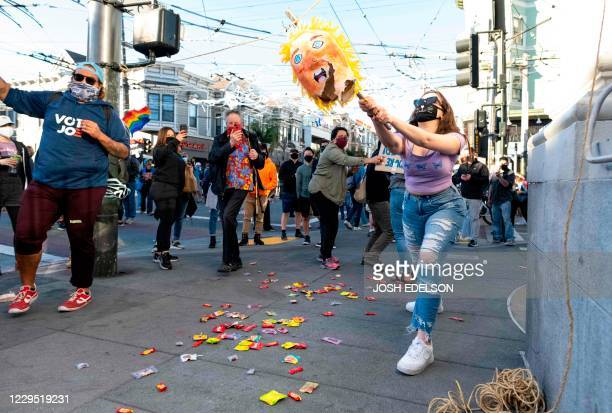 A woman smashes the head of a pinata of US President Donald Trump as people celebrate Joe Biden being elected President of the United States in the...