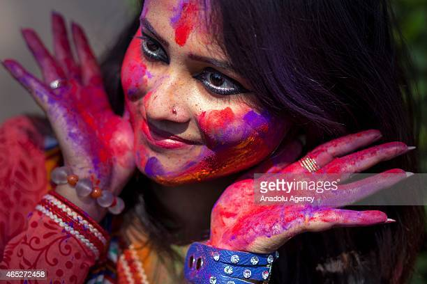 A woman smeared with colored powder takes part in celebrations of the Dol Utsav Festival a festival of the Hindu community at the time of Holi in...