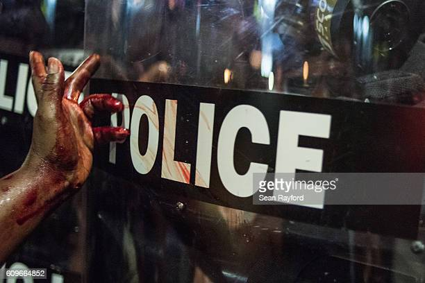A woman smears blood on a police riot shield on September 21 2016 in downtown Charlotte NC The North Carolina governor has declared a state of...