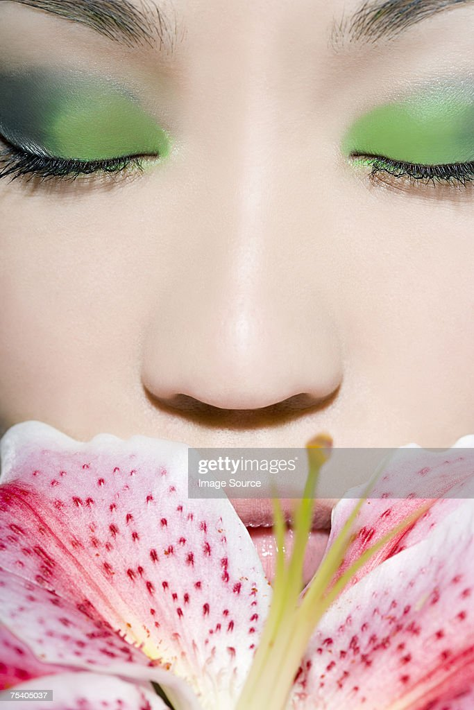 Woman smelling a flower : Stock Photo