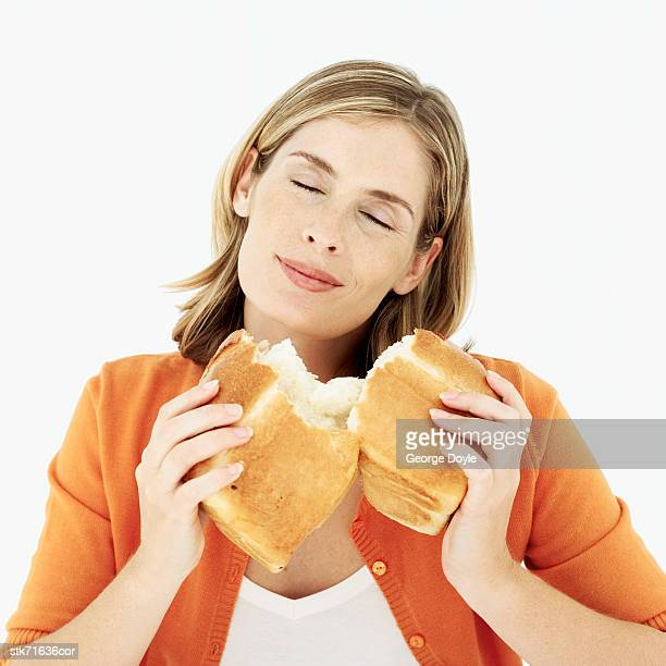 woman smelling a loaf of broken bread