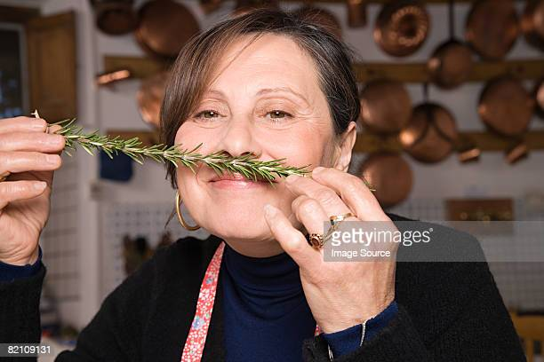 Woman smelling a sprig of rosemary
