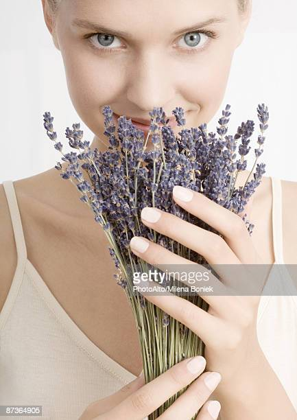 Woman smelling bunch of lavender, looking at camera