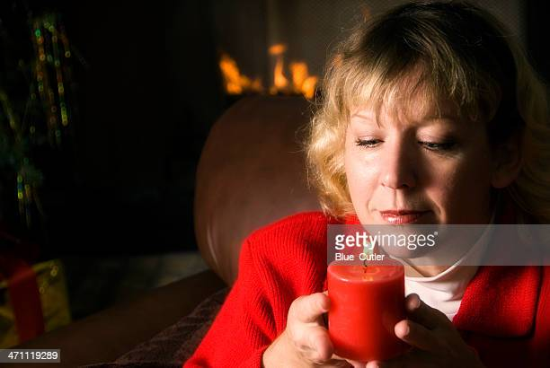 Woman Smelling Candle by the Fireplace