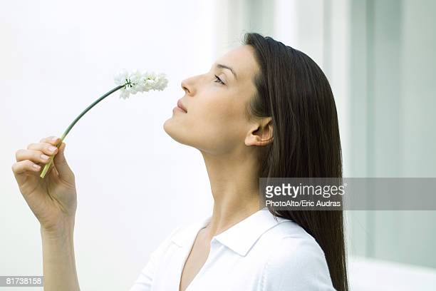 woman smelling flower, head back, side view - 黒髪 ストックフォトと画像
