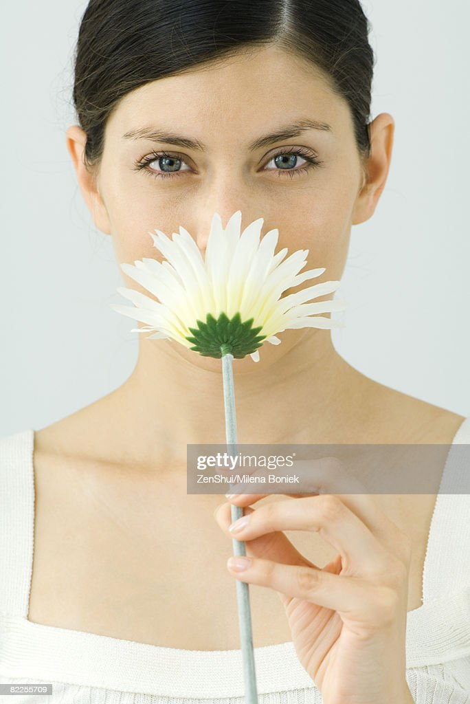 Woman smelling flower, looking at camera, portrait : Stock Photo