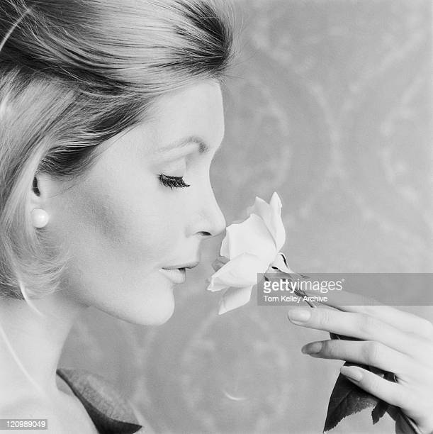 Woman smelling flower with eyes closed, close-up